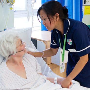 A female Filipino nurse assists an elderly woman in bed UK